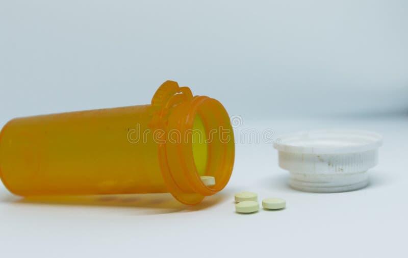 Bouteille de pilule de son côté avec des pilules tombant photographie stock libre de droits