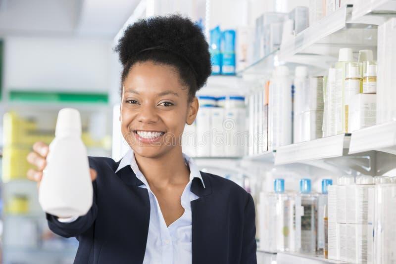 Bouteille de Smiling While Presenting de femme d'affaires dans la pharmacie image stock
