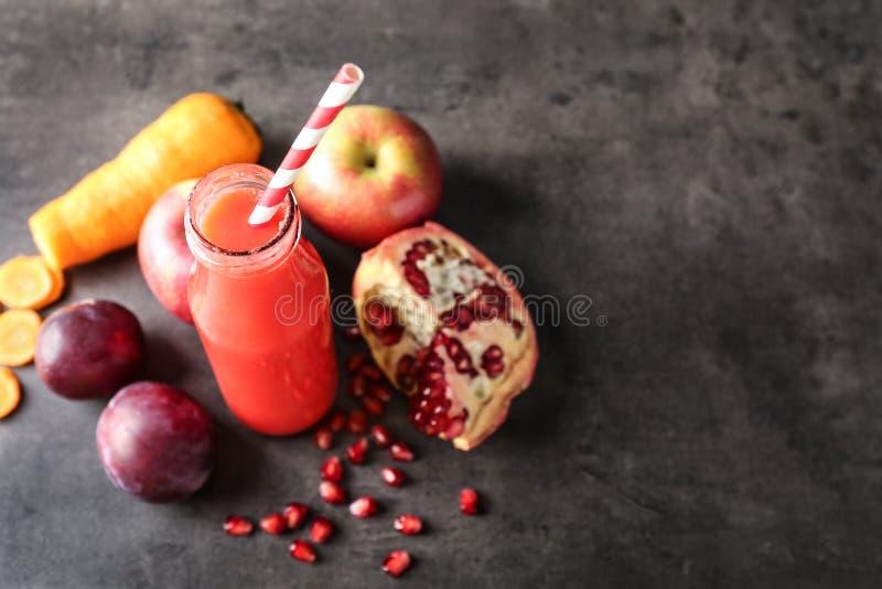 Bouteille de smoothie et d'ingrédients rouges savoureux sur la table grise images libres de droits