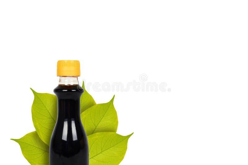 Bouteille de soja foncé ou de sauce balsamique sur le fond des feuilles D'isolement sur le blanc Nourriture asiatique, assaisonne photos stock