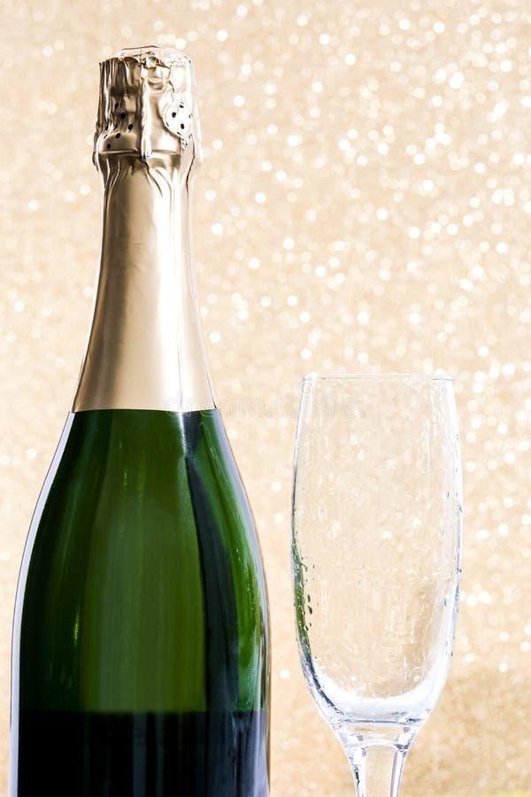 Bouteille de tasse de champagne et en verre sur le fond d'or photos stock