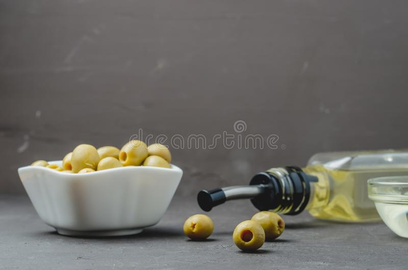 Bouteille de verre d'huile d'olive et d'olive dans un bol blanc sur fond de pierre noire Focalisation sélective Concept d'huile d images libres de droits