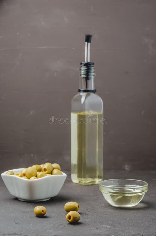 Bouteille de verre d'huile d'olive et d'olive dans un bol blanc sur fond de pierre noire Focalisation sélective Concept d'huile d image stock