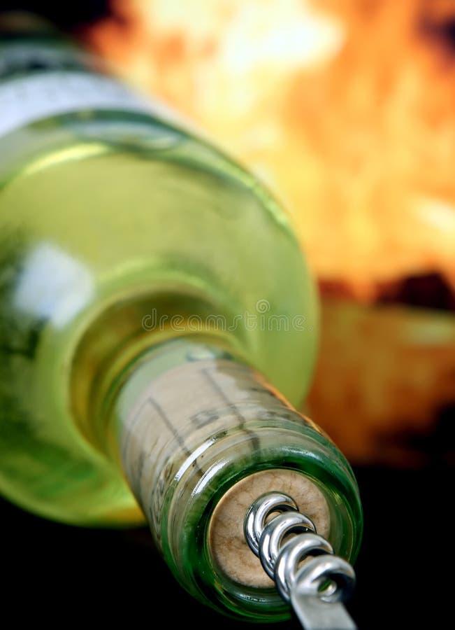 Bouteille de vin blanc par l'incendie rouge avec le tire-bouchon image stock