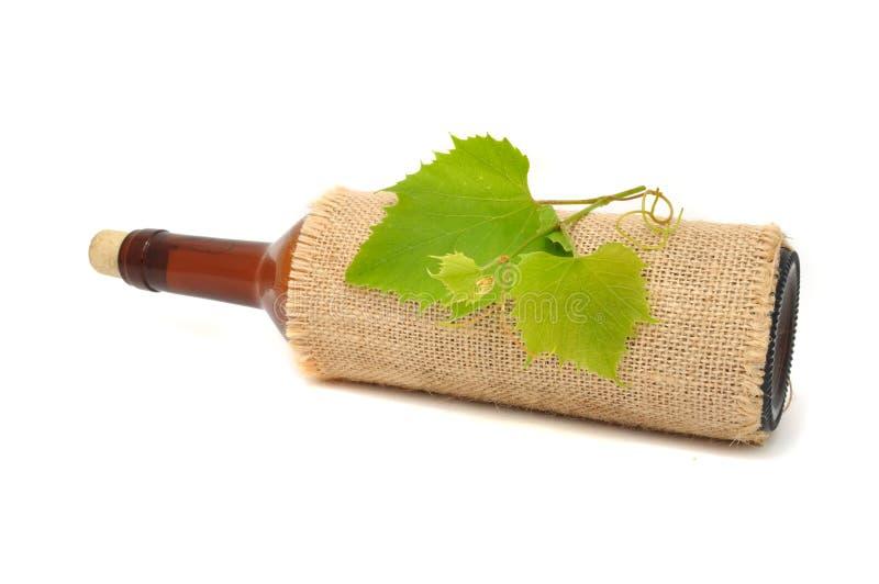 Bouteille de vin dans la toile à sac avec la vigne photographie stock libre de droits