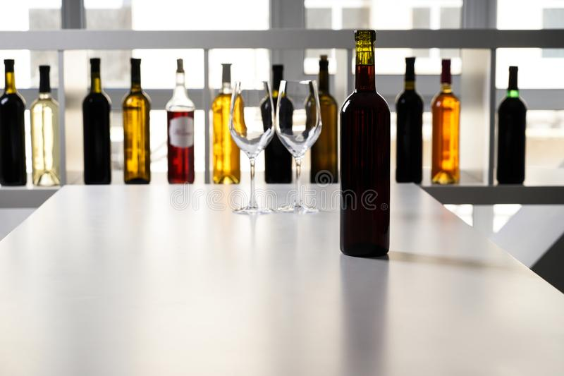 Bouteille de vin et de deux verres vides sur la table dans la barre photo libre de droits