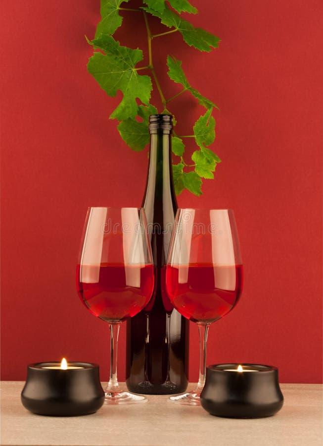 Bouteille de vin rouge avec deux verres à vin et bougies image stock