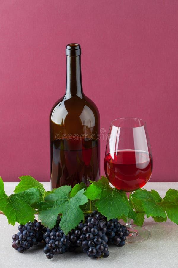 Bouteille de vin rouge avec le verre à vin et les raisins mûrs images stock