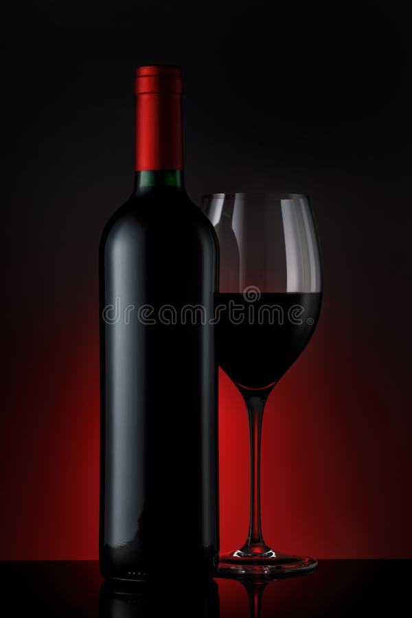 Bouteille de vin rouge avec un verre sur un fond noir images libres de droits