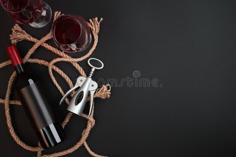 Bouteille de vin rouge, deux verres et tire-bouchon sur le fond noir Vue supérieure avec l'espace de copie photographie stock