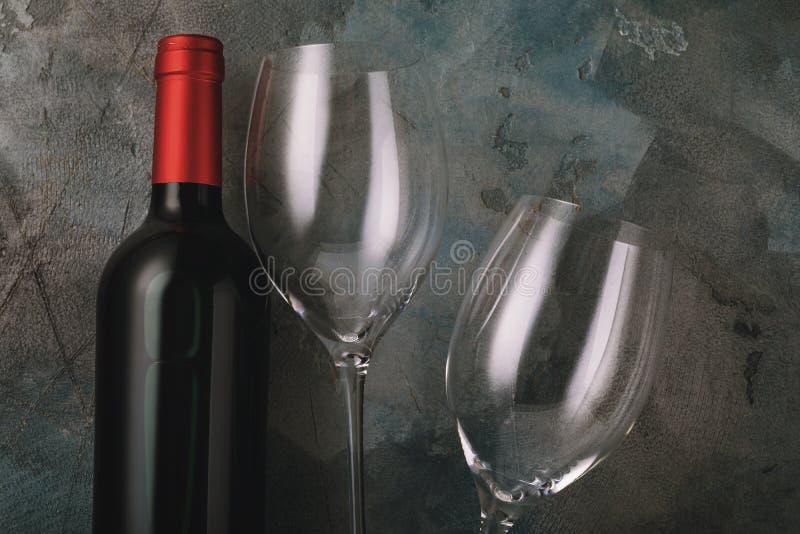 Bouteille de vin rouge et de deux verres vides images libres de droits