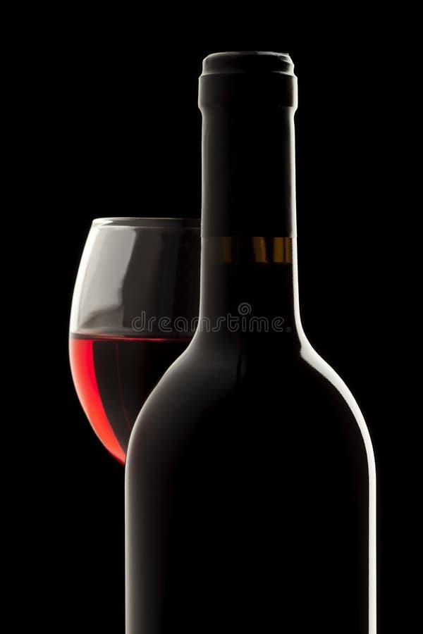 Bouteille de vin rouge et glace de vin dans un backgrou noir photographie stock