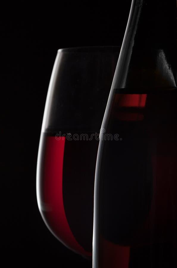 Bouteille de vin rouge et verre de vin sur le fond noir photo stock