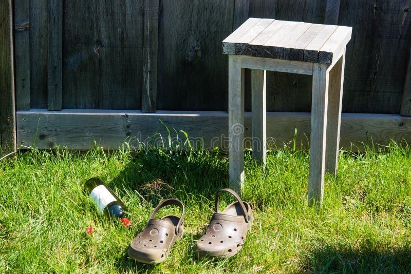 Bouteille de vin, tabouret et sandales vides sur l'herbe verte images stock