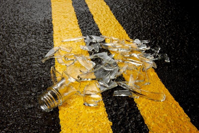 Bouteille de whiskey brisée sur la route photographie stock