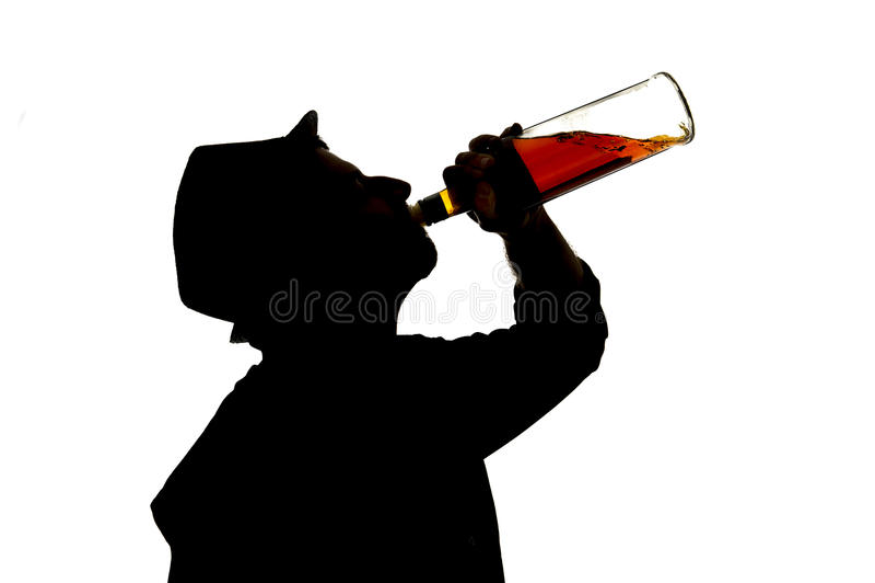Bouteille de whiskey potable bue par alcoolique d'homme en silhouette d'alcoolisme image libre de droits