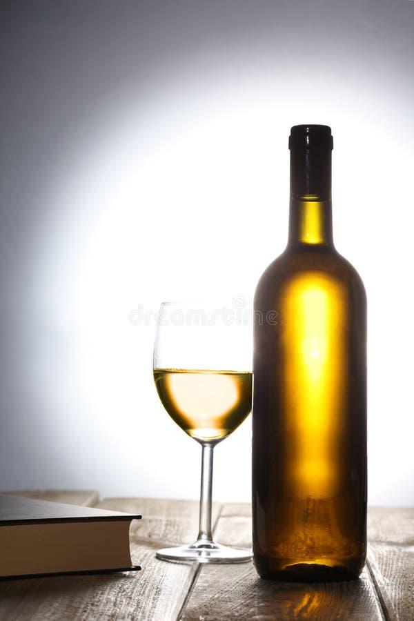 Bouteille du vin blanc, d'un verre de vin et d'un livre sur une table en bois avec l'espace de copie pour votre texte photo stock