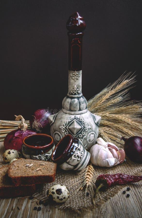 Bouteille en céramique avec des verres à liqueur image stock