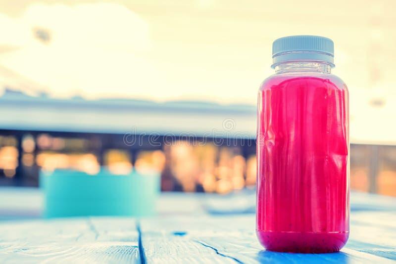 Bouteille en plastique avec la boisson de fruit rouge dans le restaurant images libres de droits
