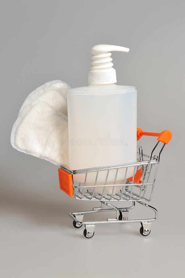 Bouteille en plastique de gel de pompe intime de distributeur, serviette sanitaire dans le chariot photographie stock