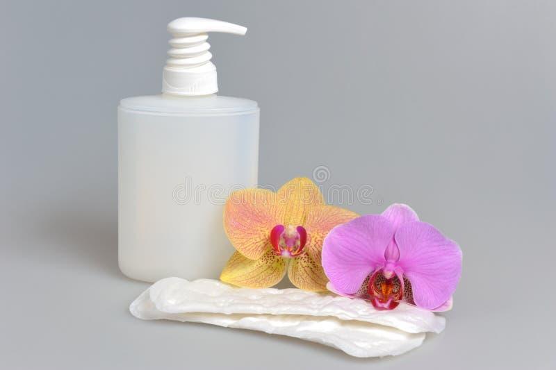 Bouteille en plastique de gel de pompe intime de distributeur, serviette sanitaire, fleurs sur le gris photos stock