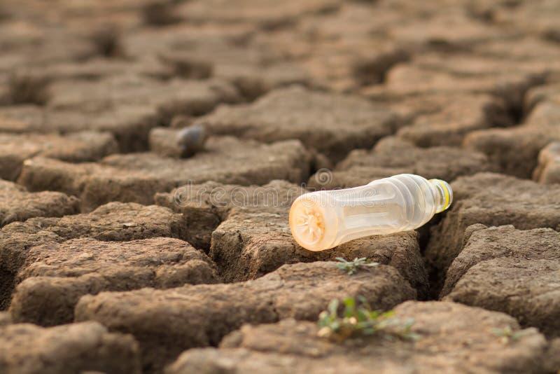 Bouteille en plastique sur la pollution au sol de métaphore de la matière plastique en eau et nature photographie stock libre de droits