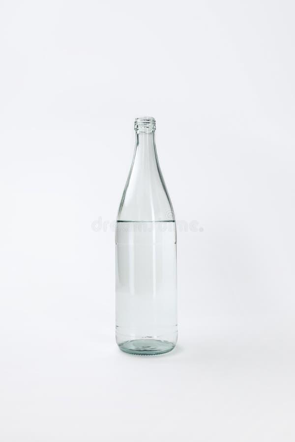 Bouteille en verre avec de l'eau minéral calme images stock