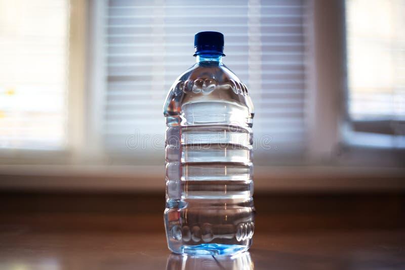 Bouteille en verre avec de l'eau sur la table images libres de droits