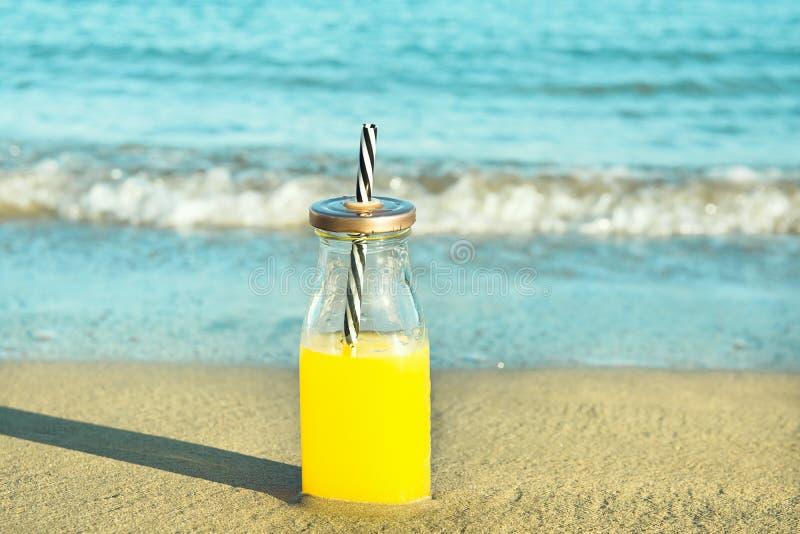 Bouteille en verre avec le jus de fruit tropicaux fraîchement pressé avec Straw Standing sur le sable de plage Vagues mousseuses  photographie stock libre de droits