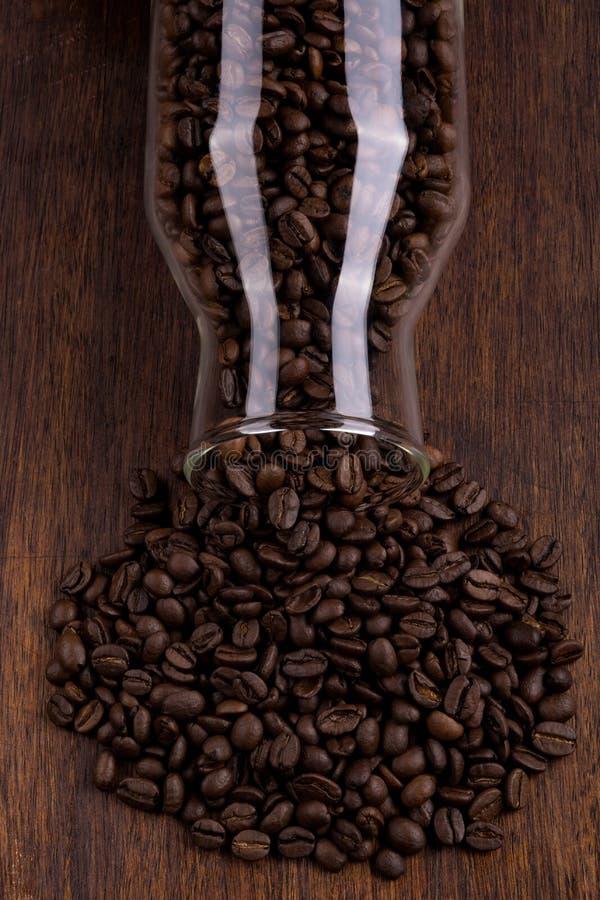 Bouteille en verre complètement de grains de café photographie stock