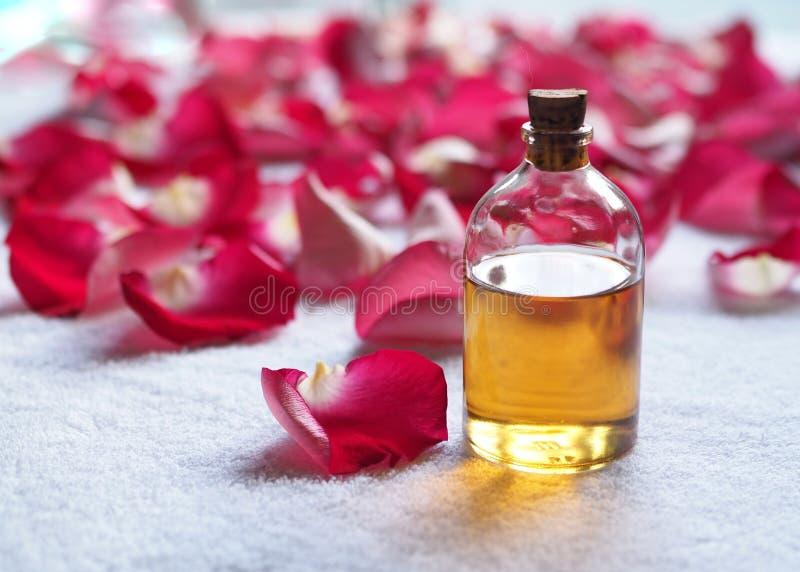 Bouteille en verre d'huile d'arome parmi les pétales de rose rouges sur la serviette éponge blanche STATION THERMALE et détendre  photo libre de droits
