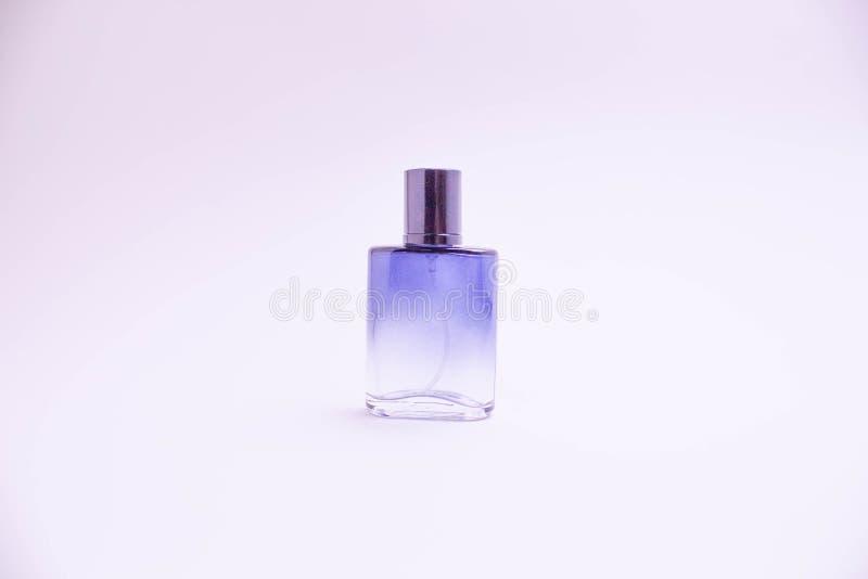Bouteille en verre de parfum sur le fond blanc Rose, bouteille bleue, verte, noire Femmes et parfum des hommes Aromatherapy, stat photos stock