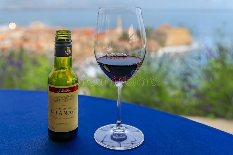 Bouteille en verre et petite de vin rouge avec la vieille ville de Budva et la Mer Adriatique dans Monténégro à l'arrière-plan photos stock