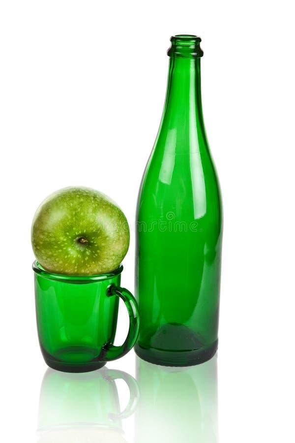 Bouteille et cuvette en verre, et pomme verte photos libres de droits