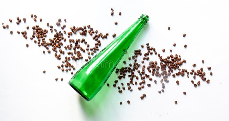 Bouteille et grains de café propres verts sur un fond blanc image libre de droits