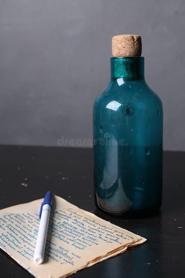 Bouteille et le livre sur la table photo stock