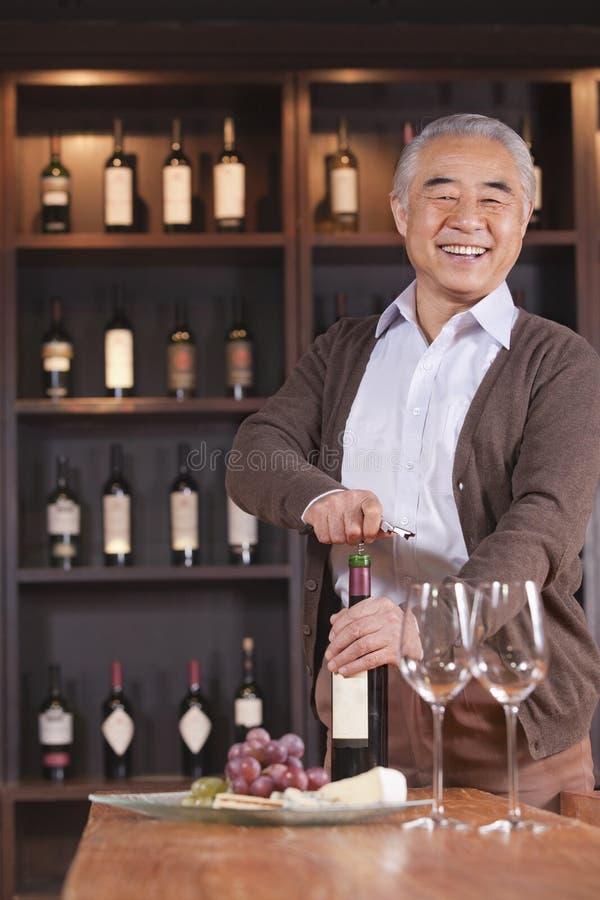 Bouteille et regarder de vin de sourire d'ouverture d'homme supérieur l'appareil-photo, étagère avec du vin à l'arrière-plan images libres de droits