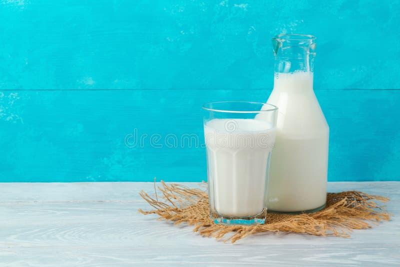 Bouteille et verre à lait sur la table en bois au-dessus du fond bleu avec l'espace de copie Vacances juives Shavuot photographie stock libre de droits