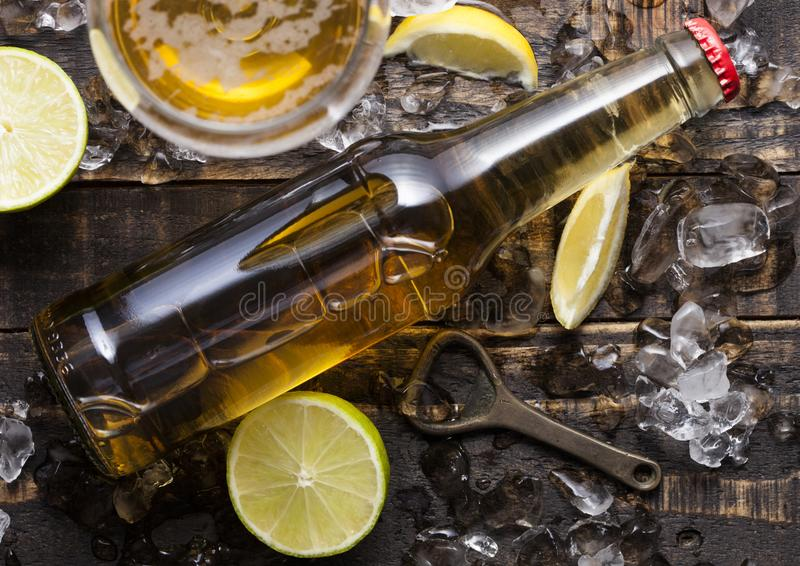 Bouteille et verre de bière blonde avec le citron et la chaux photographie stock