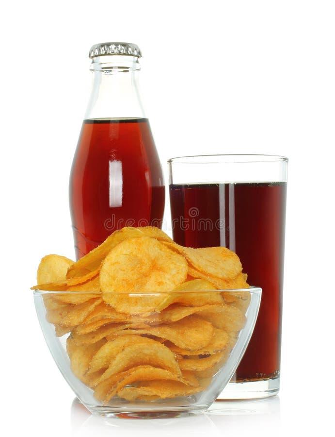 Bouteille et verre de kola avec des pommes chips photos stock