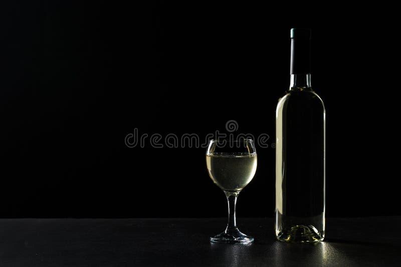 Bouteille et verre de vin avec du vin blanc sur le fond foncé images stock
