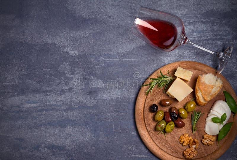 Bouteille et verre de vin avec du fromage, les olives, le pain, les écrous et le romarin sur le fond foncé Concept de vin et de n images libres de droits