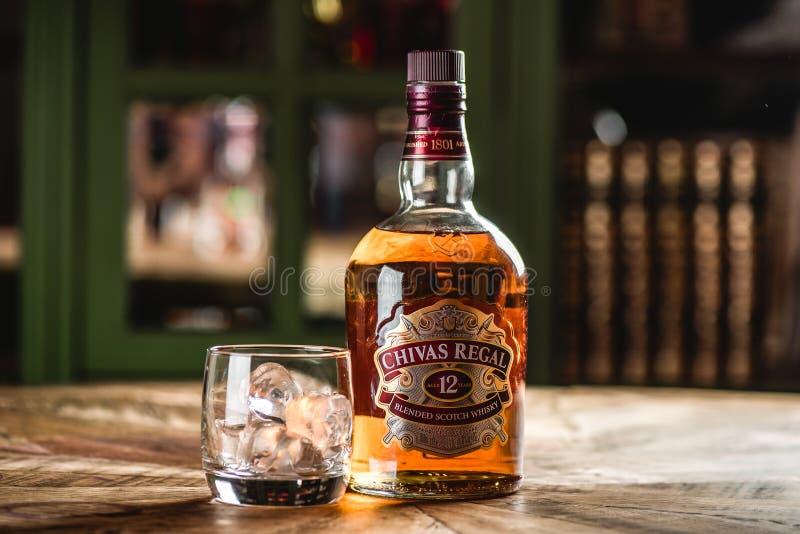 Bouteille et verre de whiskey de Chivas Regal avec des glaçons sur t en bois photographie stock libre de droits