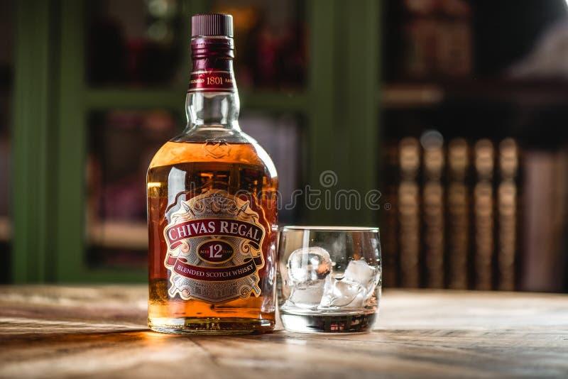Bouteille et verre de whiskey de Chivas Regal avec des glaçons sur t en bois photos libres de droits
