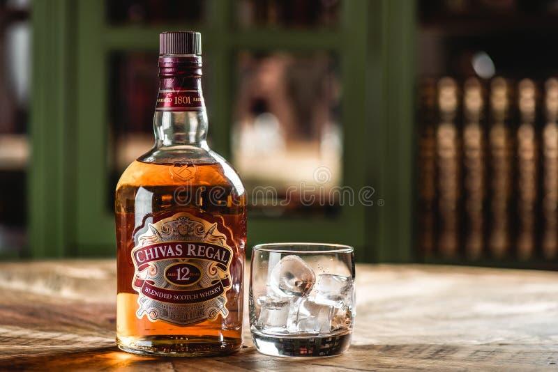 Bouteille et verre de whiskey de Chivas Regal avec des glaçons sur t en bois image libre de droits