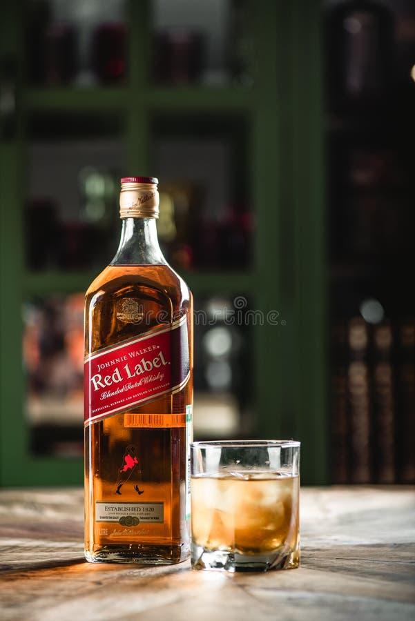 Bouteille et verre de whiskey rouges de label avec des glaçons sur le tabl en bois image libre de droits