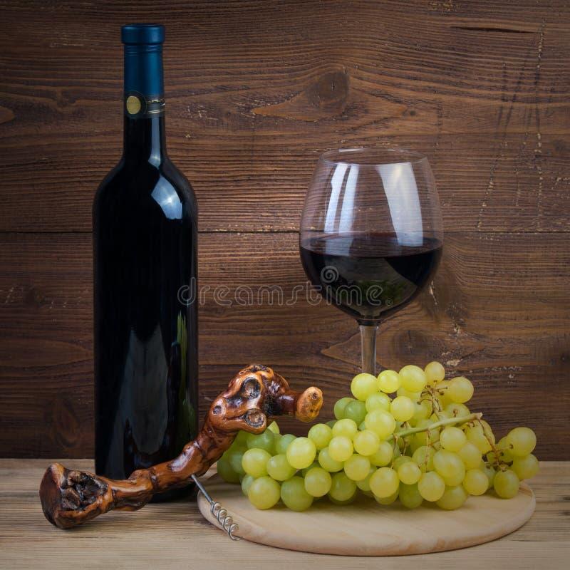Bouteille et verre du vin rouge, des raisins et du tire-bouchon faits en vigne image libre de droits