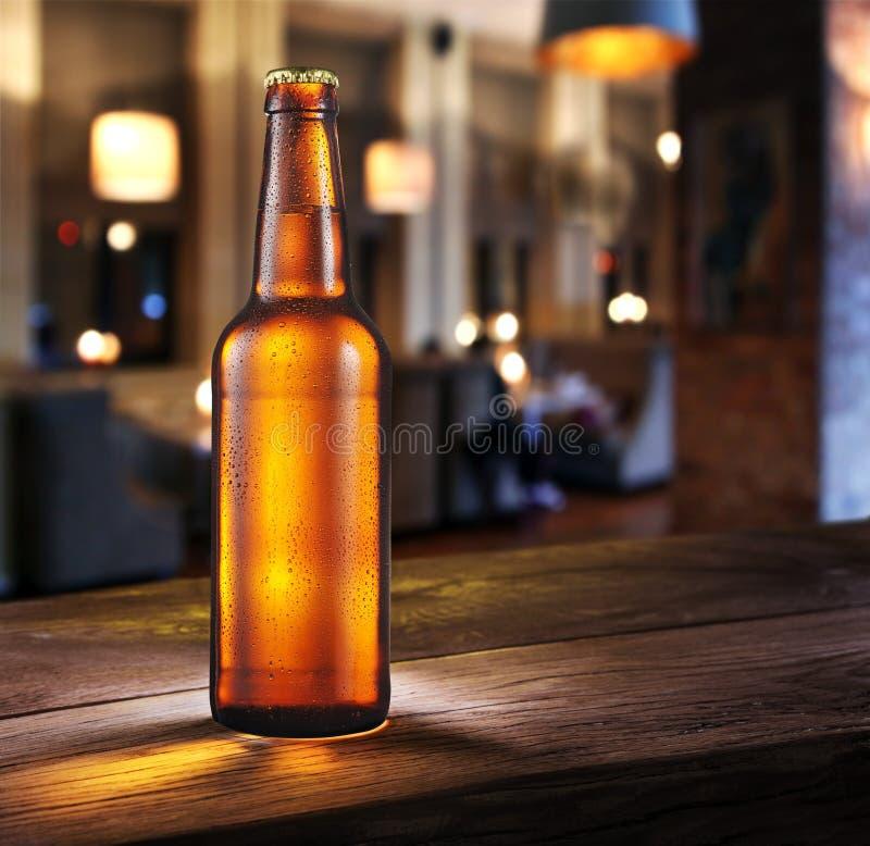 Bouteille givrée de bière blonde sur le compteur de barre photographie stock
