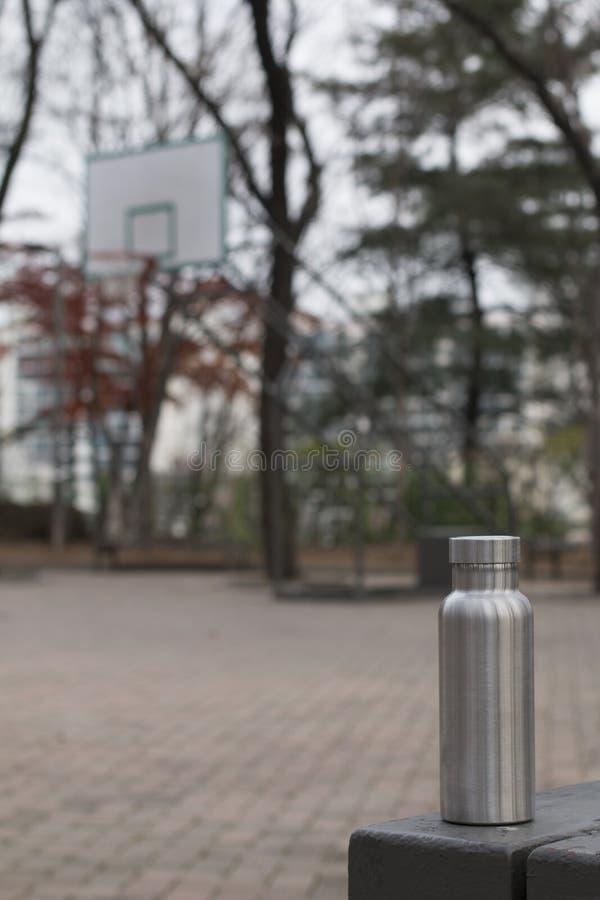 Bouteille inoxydable isolée avec un cercle de basket-ball à l'arrière-plan d'hiver photo libre de droits