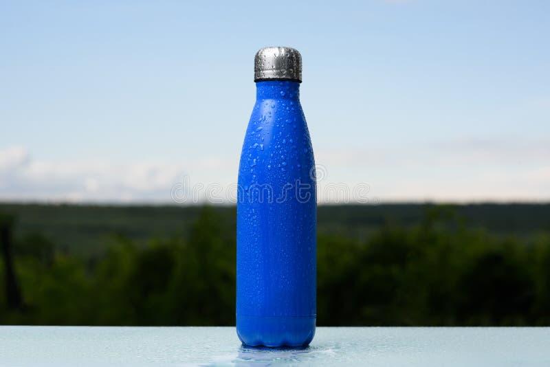 Bouteille inoxydable thermo, pulvérisée avec de l'eau Ciel et forêt sur le fond Sur le bureau en verre Thermos de couleur bleue m photographie stock libre de droits